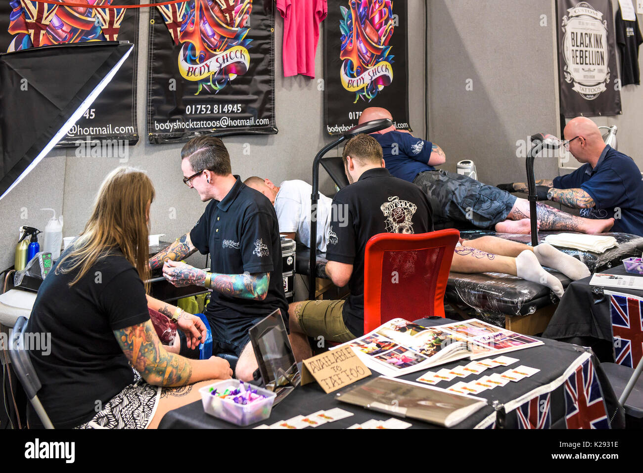 Cornwall Tattoo Convention - Tattooists working on their customers at the Cornwall tattoo Convention. Stock Photo