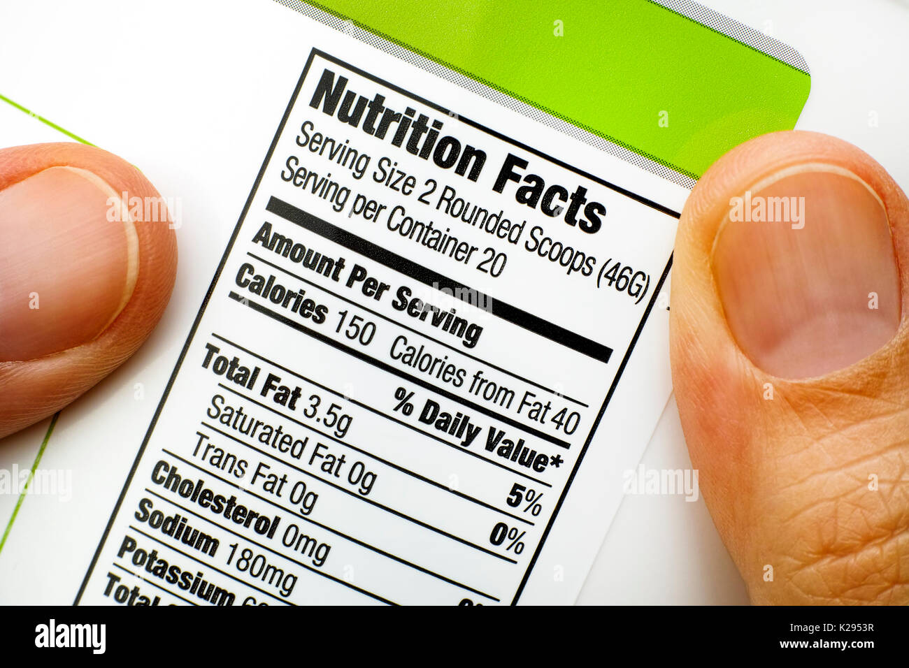 Woman fingers with protein jar. Reading nutrition facts.  Close-up. - Stock Image