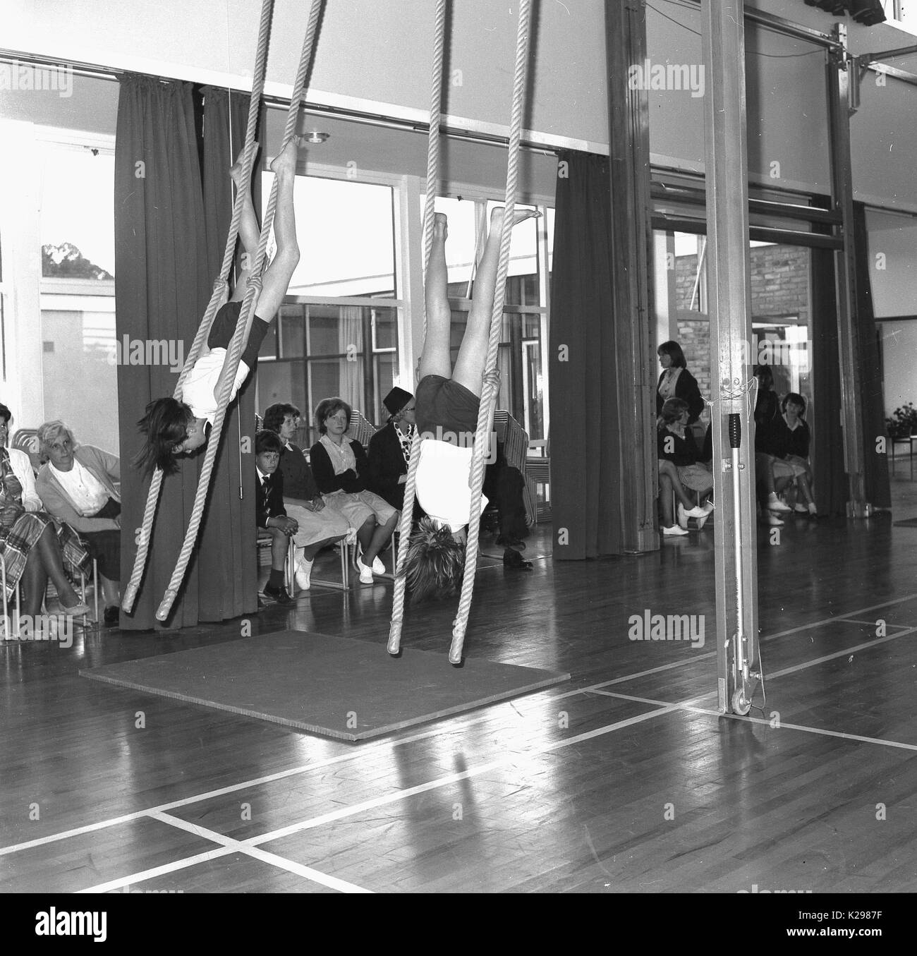 1960s, historical, picture shows two school girl gymnasts in tradittional PE kit performing an artistic routine on the climbing ropes infront of parents, England, UK. - Stock Image