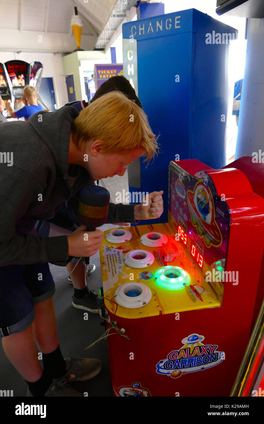 boy playing on machine in an amusement arcade - Stock Image