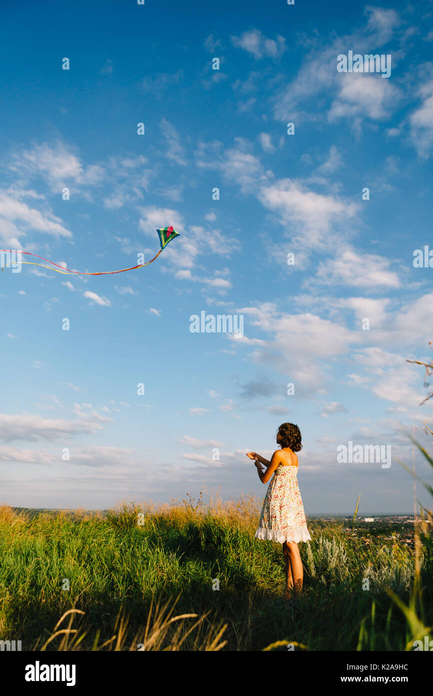 Girl playing with kite in field - Stock Image