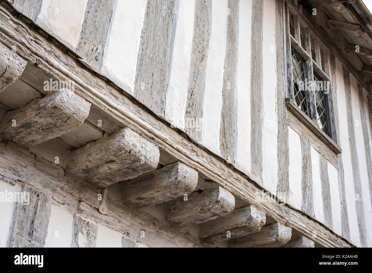 Lavenham Suffolk, detail of medieval lime-washed oak beams on the jettied front of the Guildhall in Lavenham, Suffolk. - Stock Image