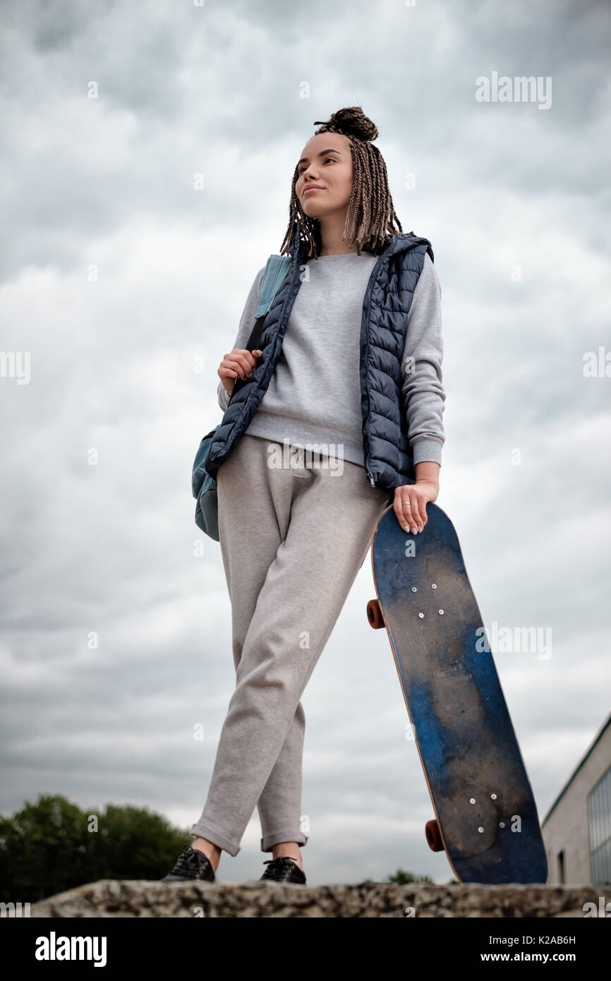 Beautiful hipster girl with skate board standing with smile - Stock Image