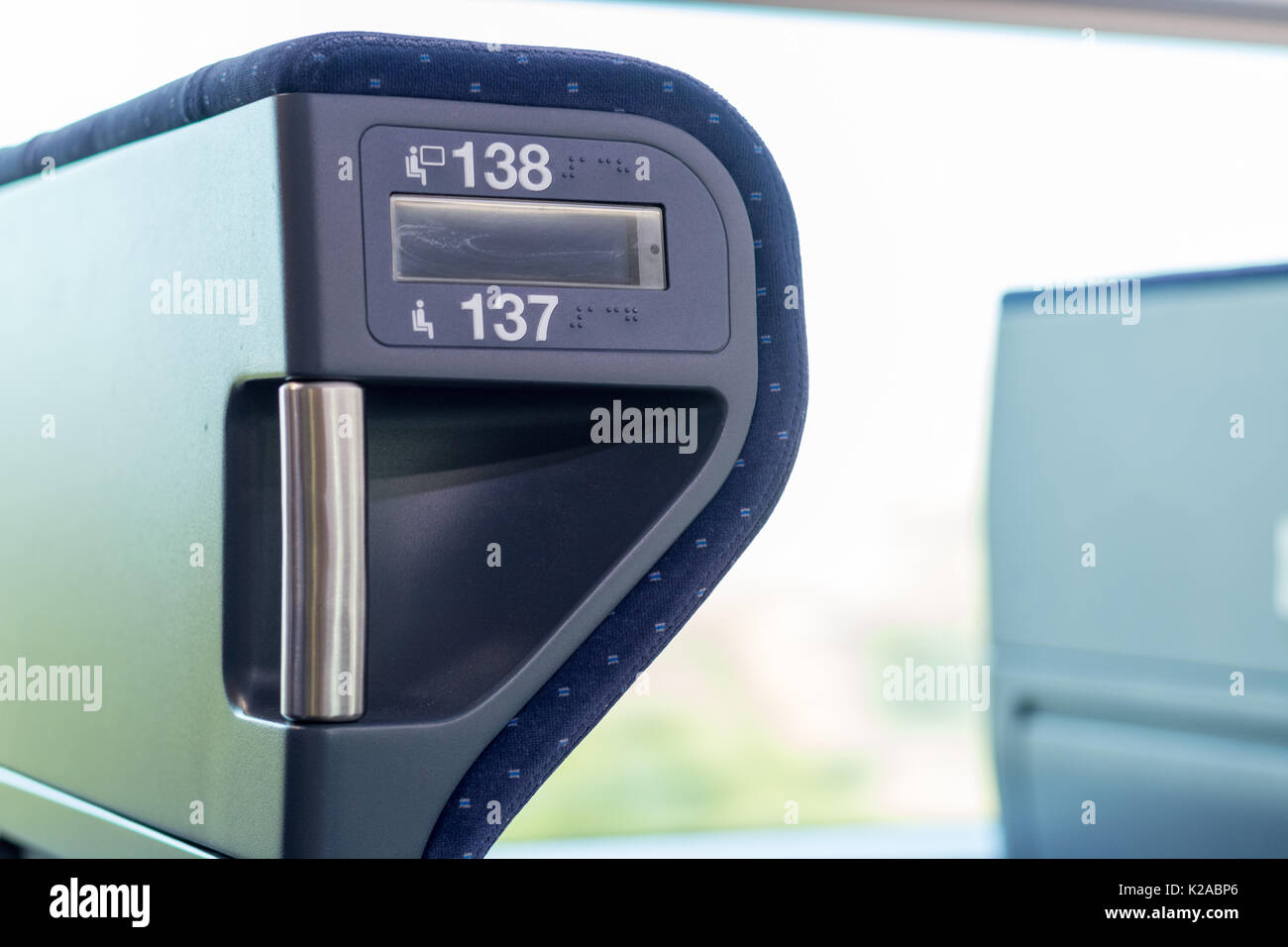Blue train seats numbers whit bright window close up - Stock Image