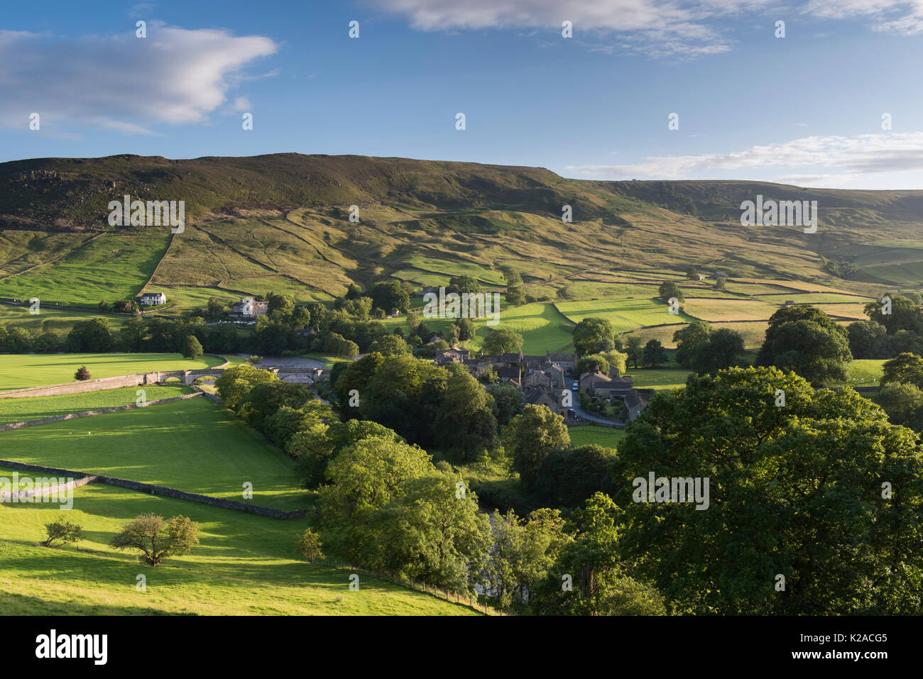 High view over beautiful, sunny Yorkshire Dales village of Burnsall in valley by River Wharfe & with steep, green, Stock Photo