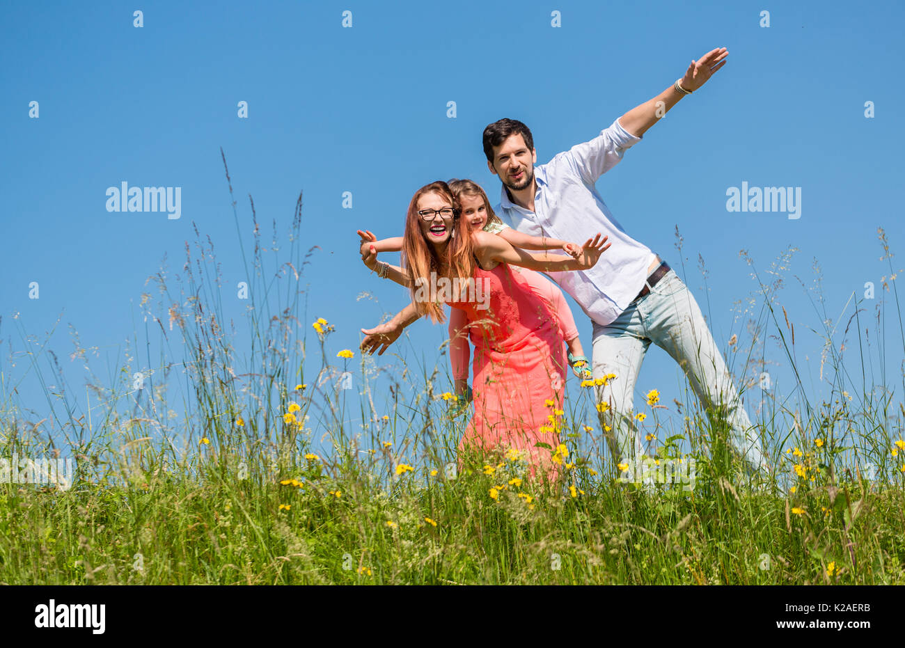 Family doing the plane on summer meadow - Stock Image