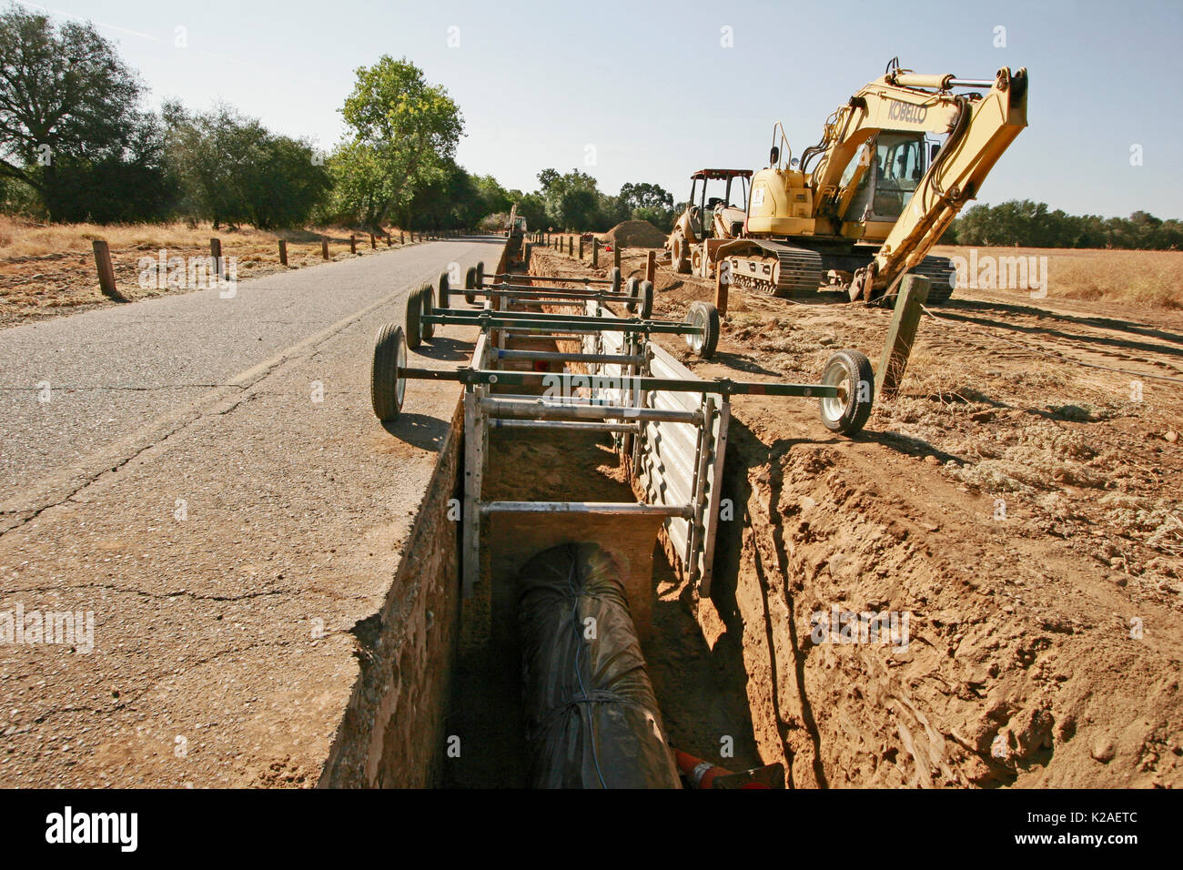 TRACKED EXCAVATOR AT DIG SITE AND VIEW ALONG DITCH WITH SAFETY SHORING BOX, CALIFORNIA - Stock Image