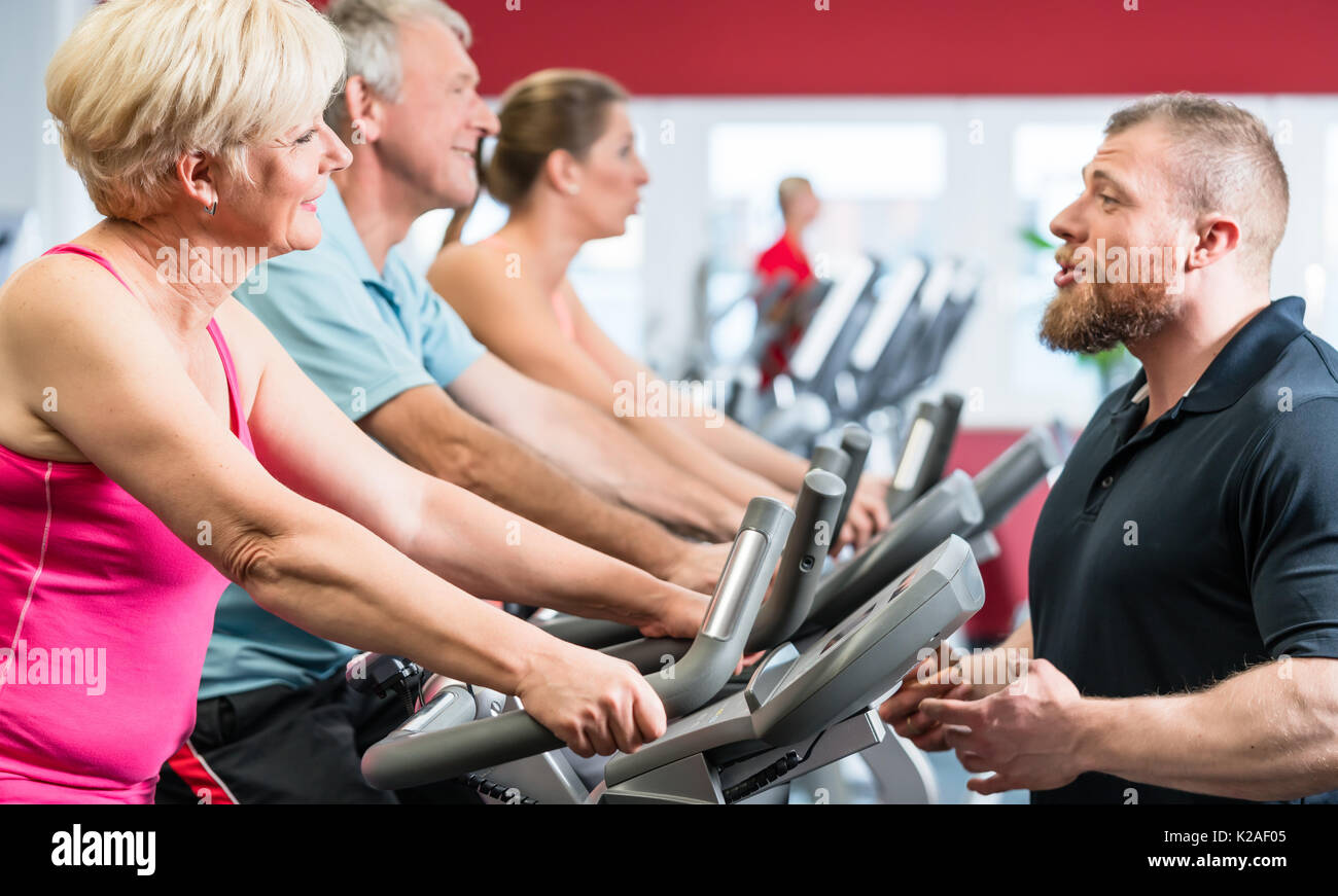 Personal trainer instructs senior woman about spinning at the gy - Stock Image