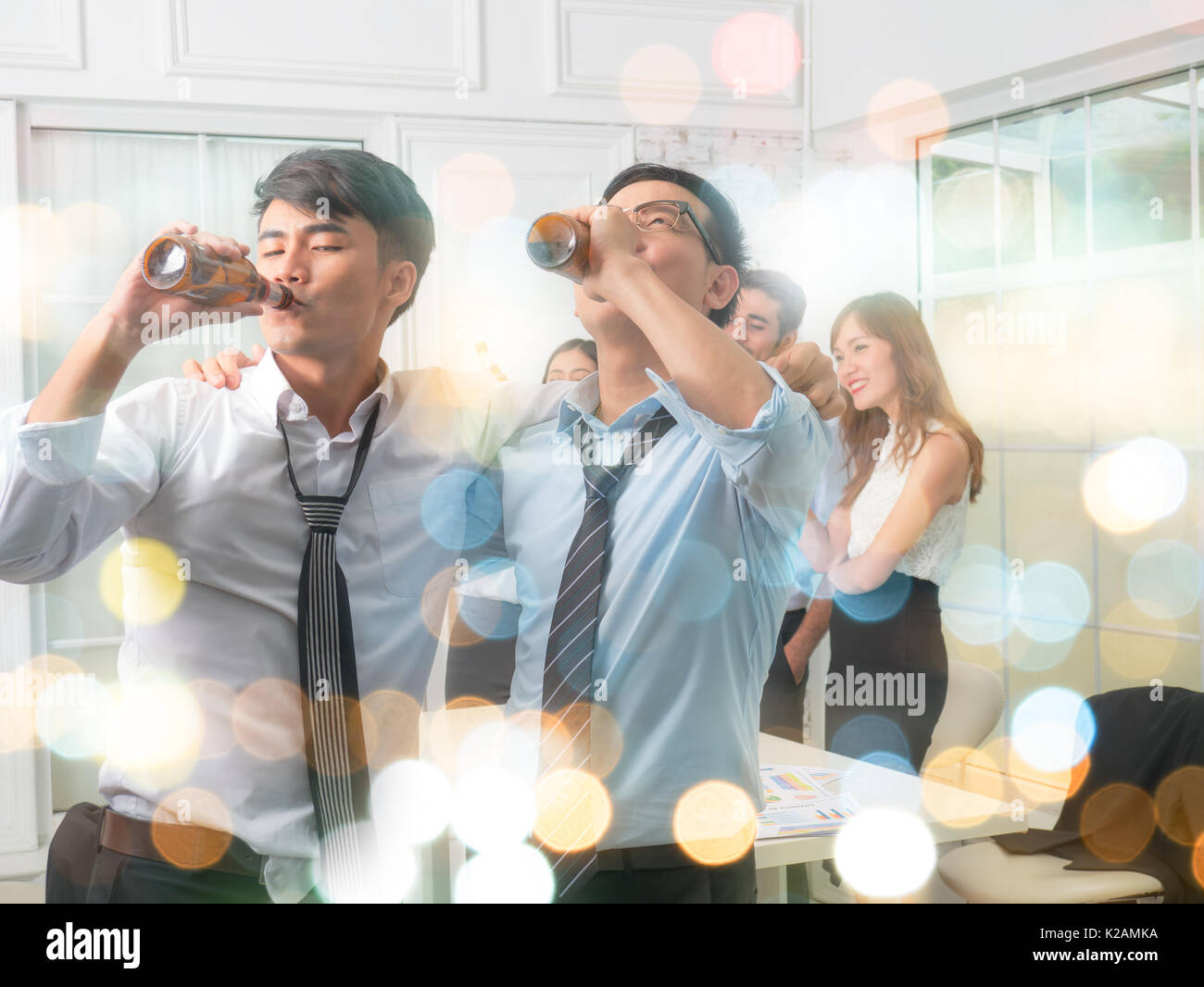 Businessmen are celebrating. After the big project succeeded. On blurred bokeh background - Stock Image