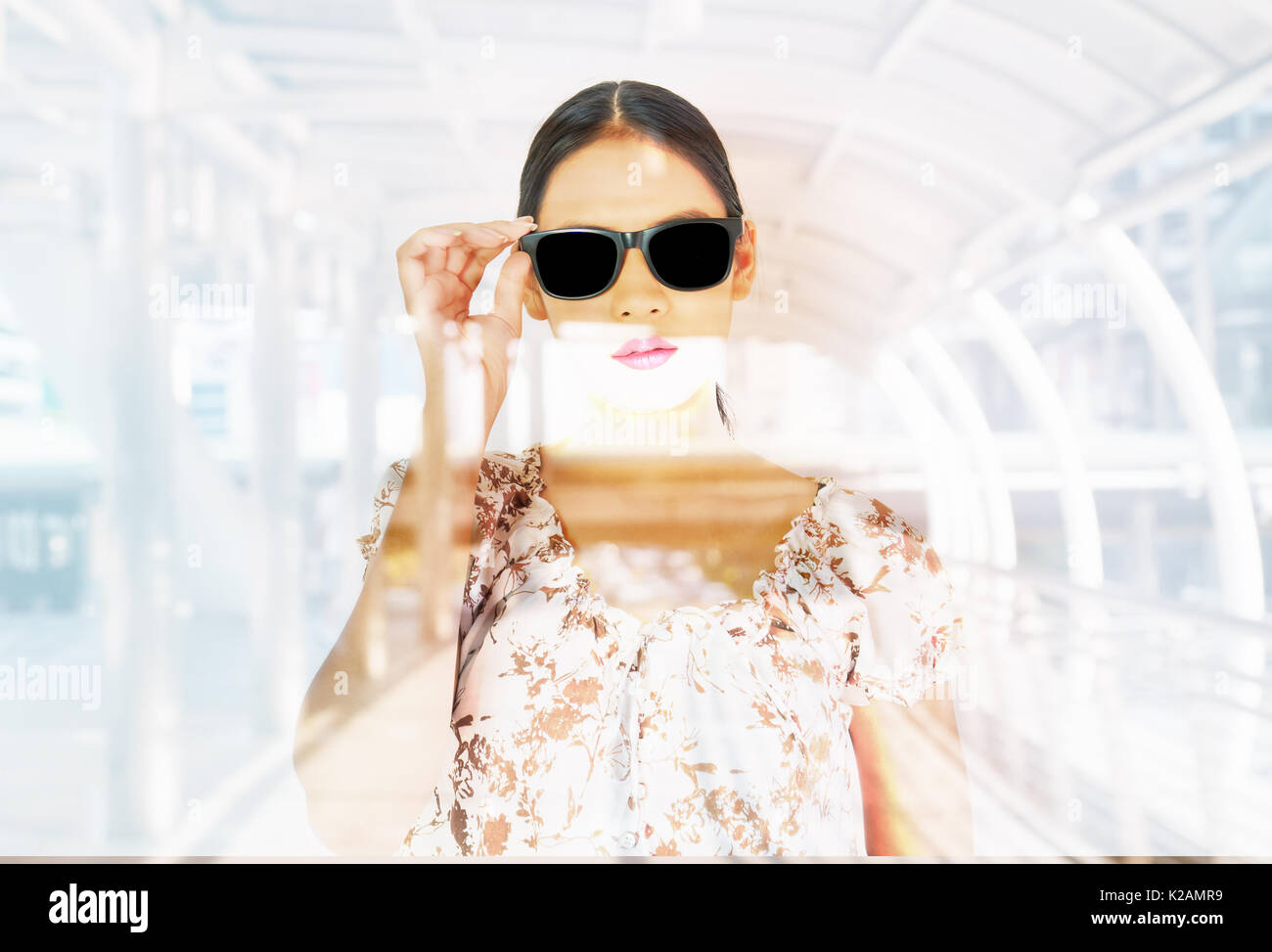 Beautiful woman wearing sunglass on blurred or de focused modern city walkway for background - Stock Image