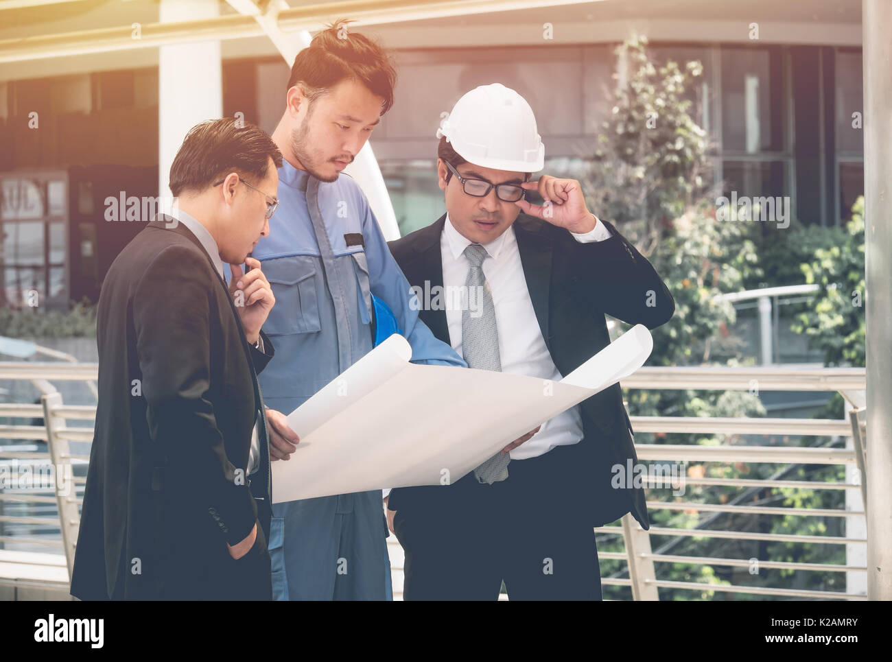Team of architects and engineer at outdoor building and talking to planning work - Stock Image