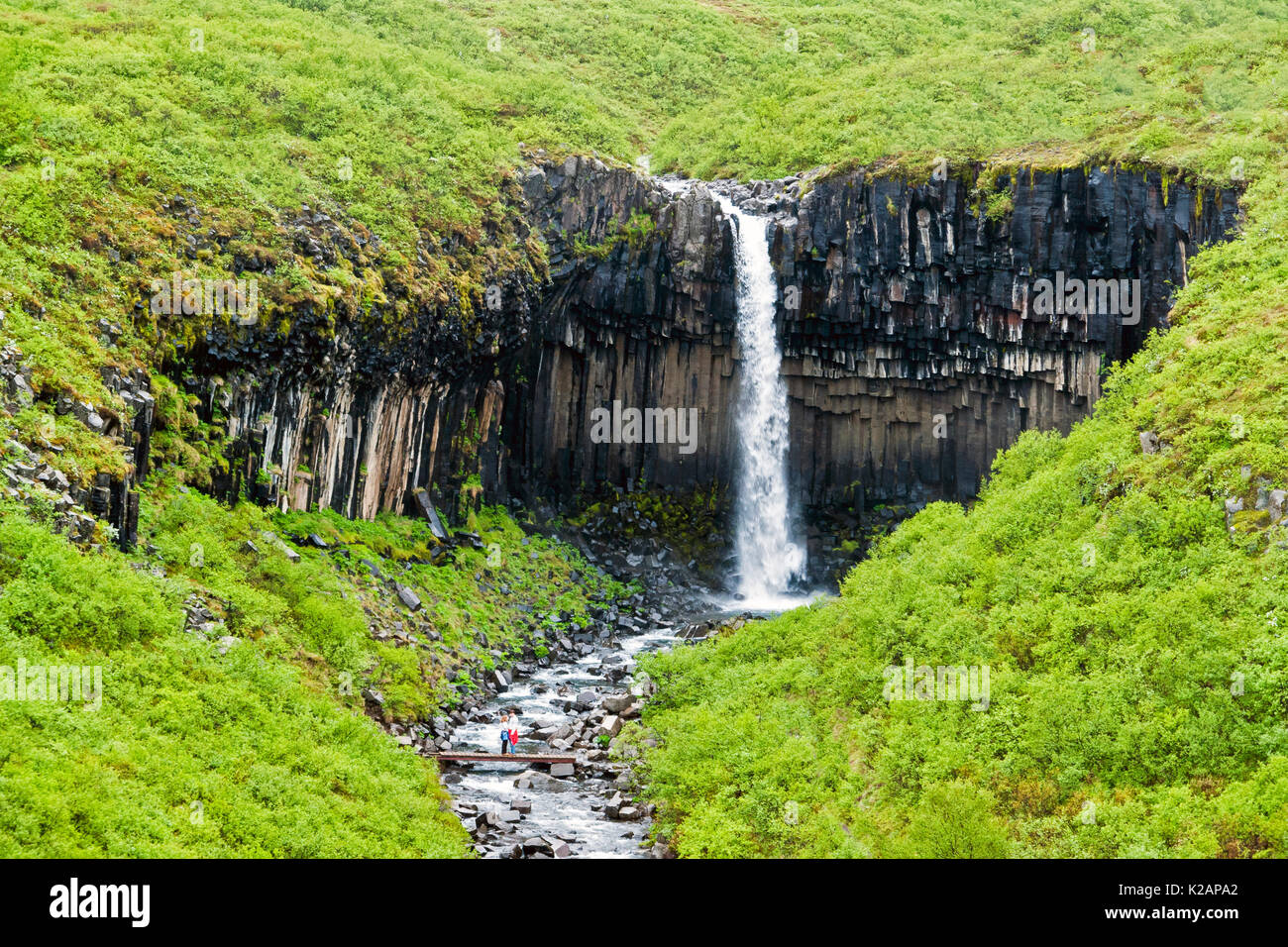 Svartifoss Waterfall in Skaftafell with isolated couple - Iceland Stock Photo