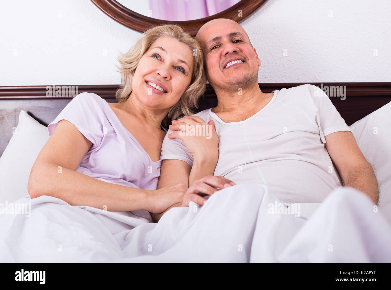 Positive mature adults posing in family bed and smiling - Stock Image