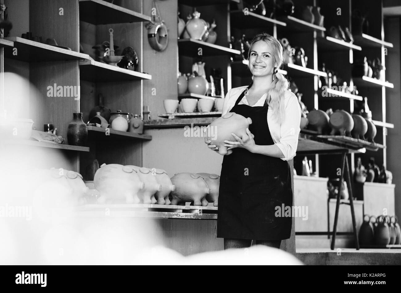 glad female artisan having ceramics in hands and standing in workshop - Stock Image