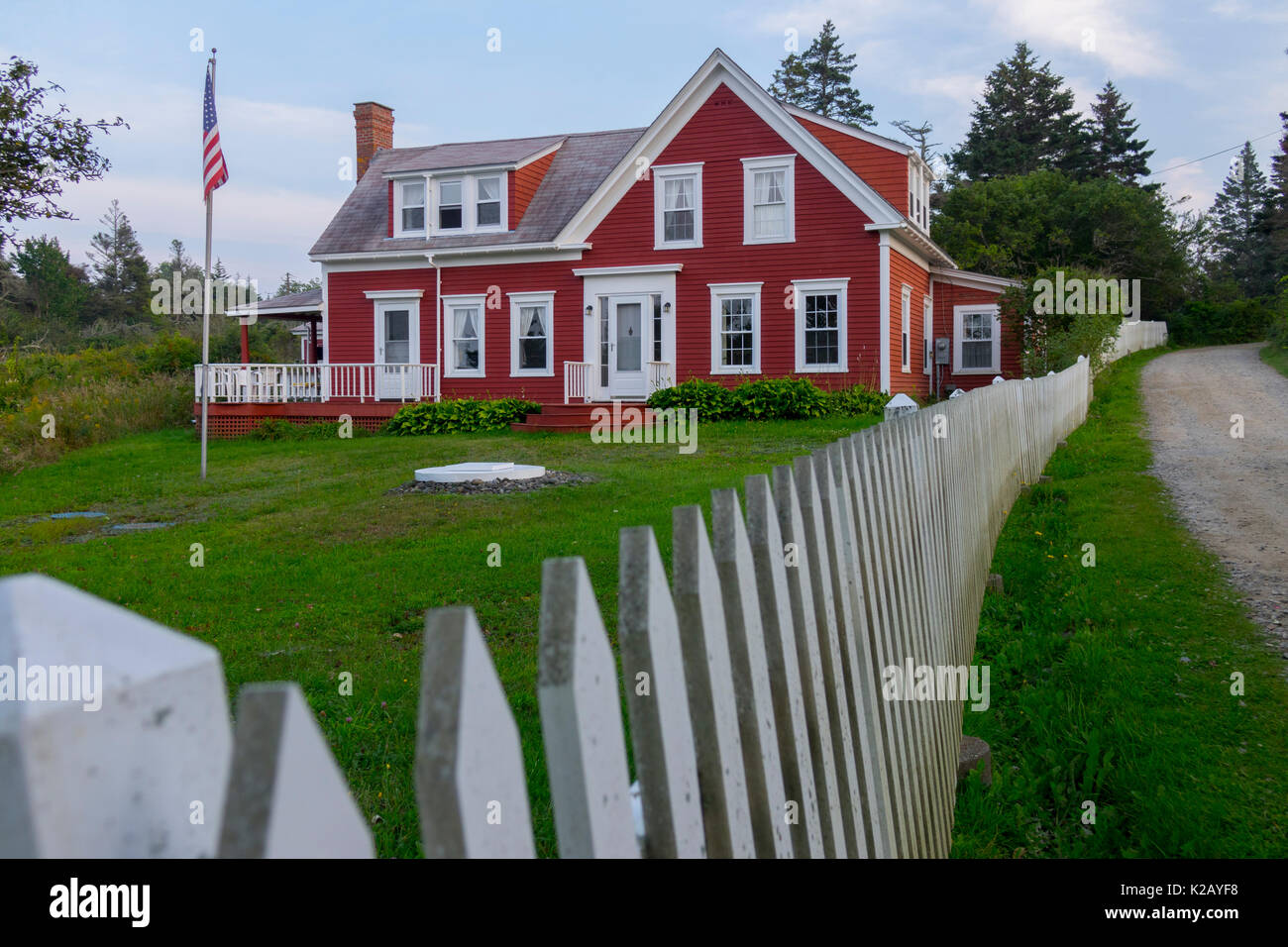 USA Maine ME Monhegan Island A red house on Lobster Cover Road with a white picket fence - Stock Image