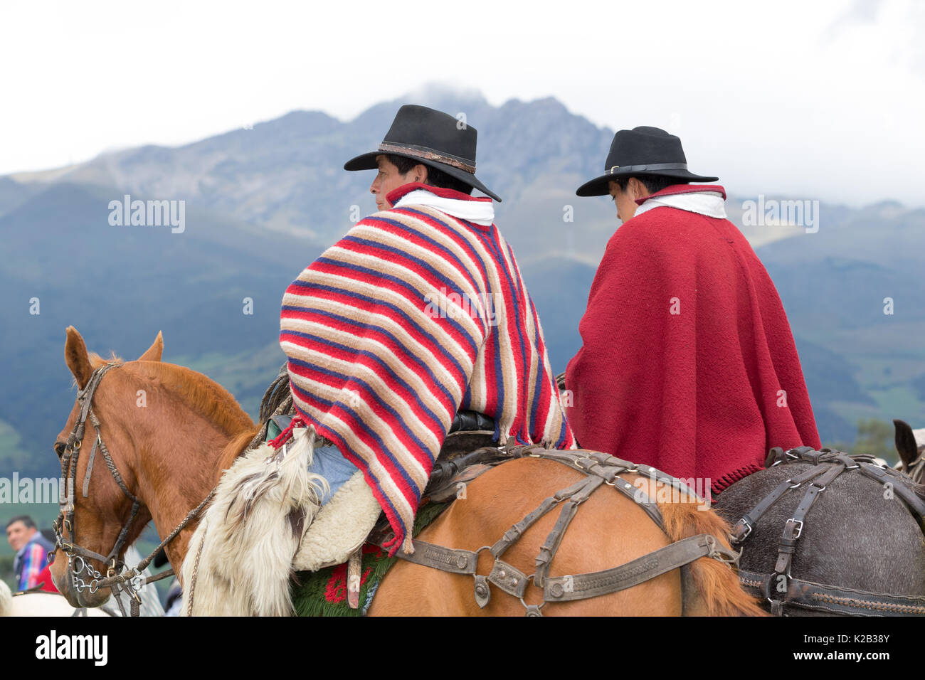 June 3, 2017 Machachi, Ecuador: closeup of indigenous quechua cowboys on horseback  dressed traditionally in colorful poncho with mountains in the bac - Stock Image