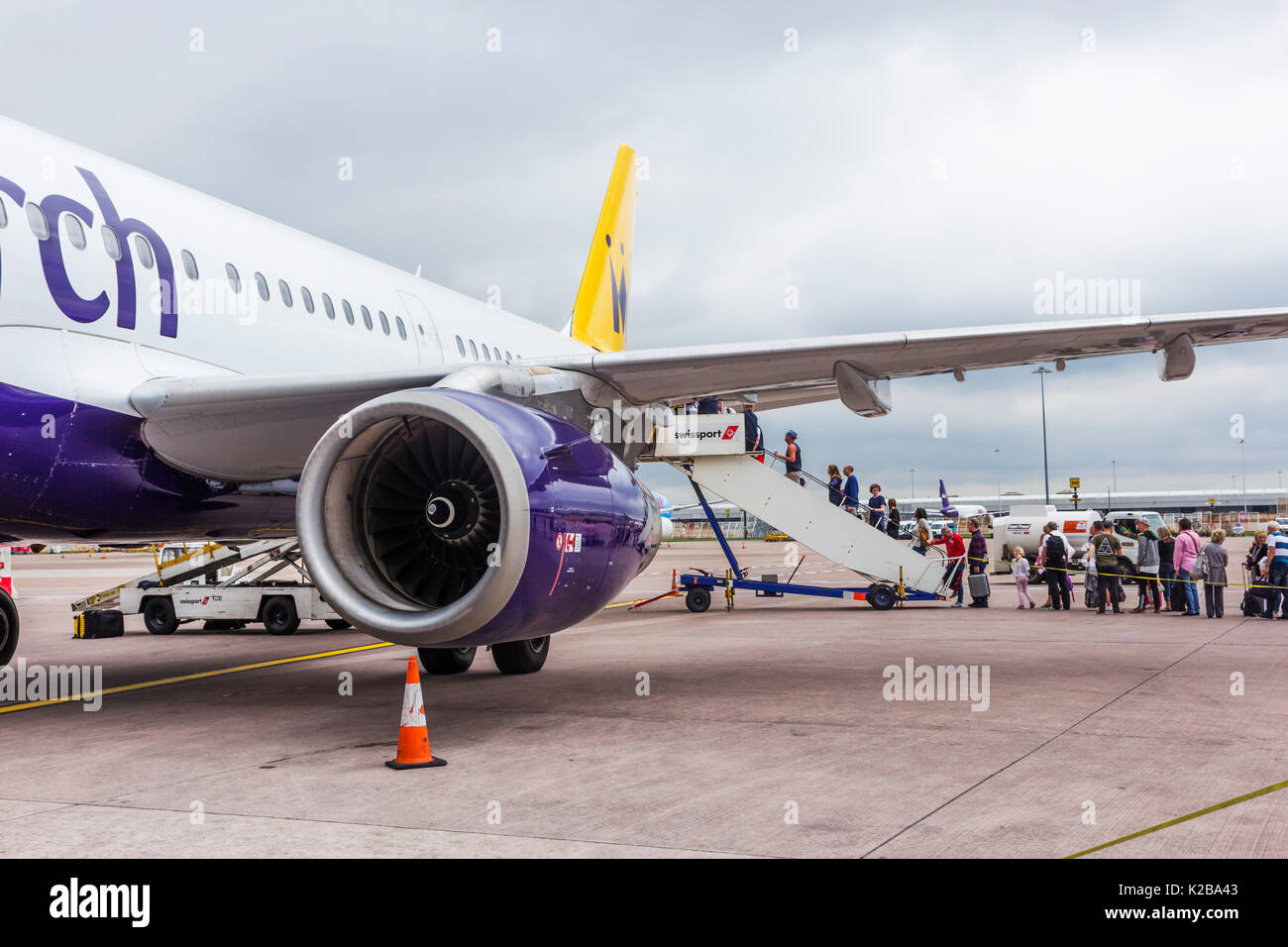 Passengers boarding a Monarch Airlines flight leaving for Spain from cloudy Manchester. - Stock Image