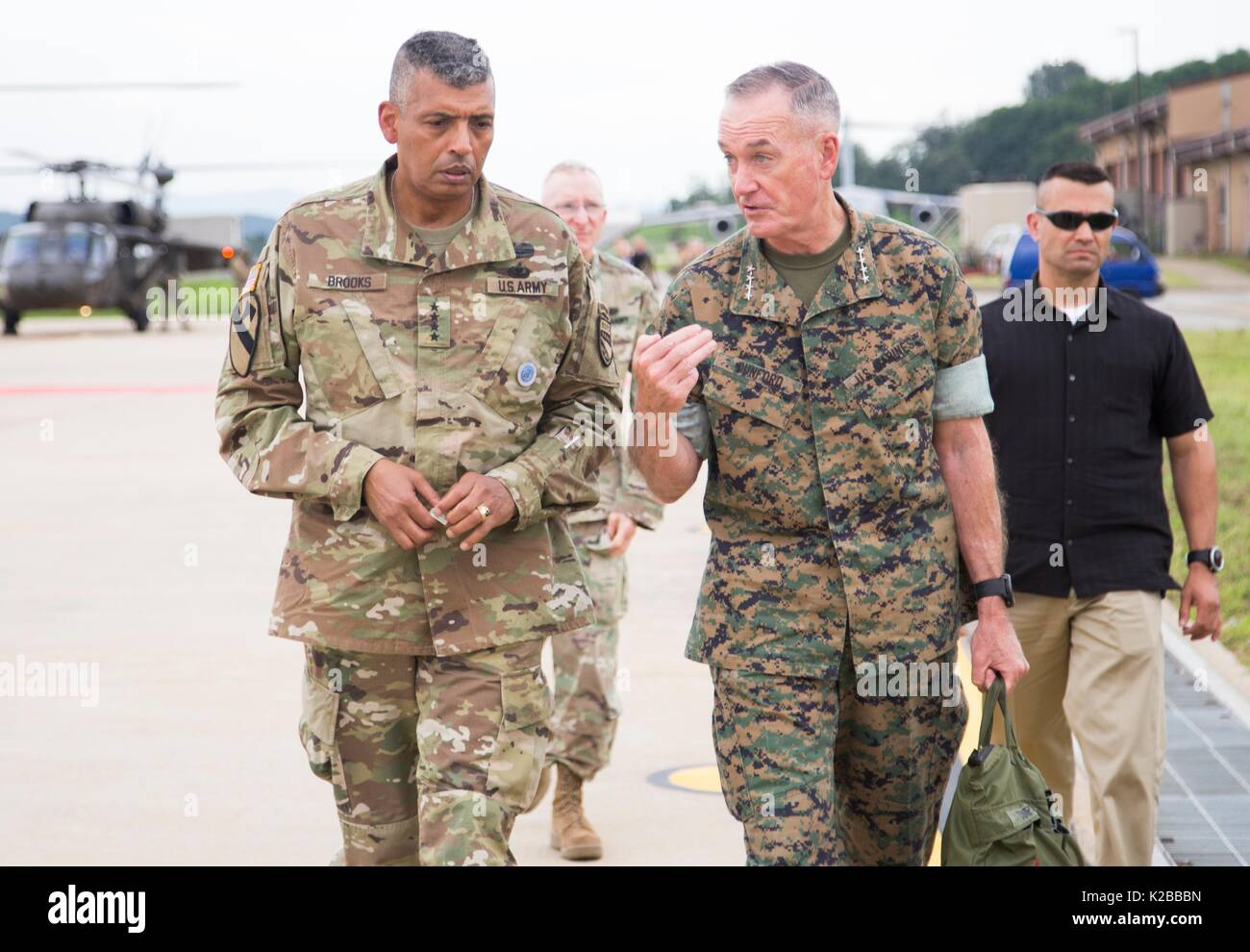 U.S. Chairman of the Joint Chiefs Gen. Joseph Dunford, right, is escorted by Army Gen. Vincent Brooks, commander, U.S. Forces Korea, on arrival at Osan Air Base August 13, 2017 in Pyeongtaek, Gyeonggi-do, South Korea. Dunford is meeting military leaders in the Asia-Pacific region as tensions rise with North Korea over nuclear and ballistic missiles tests. - Stock Image