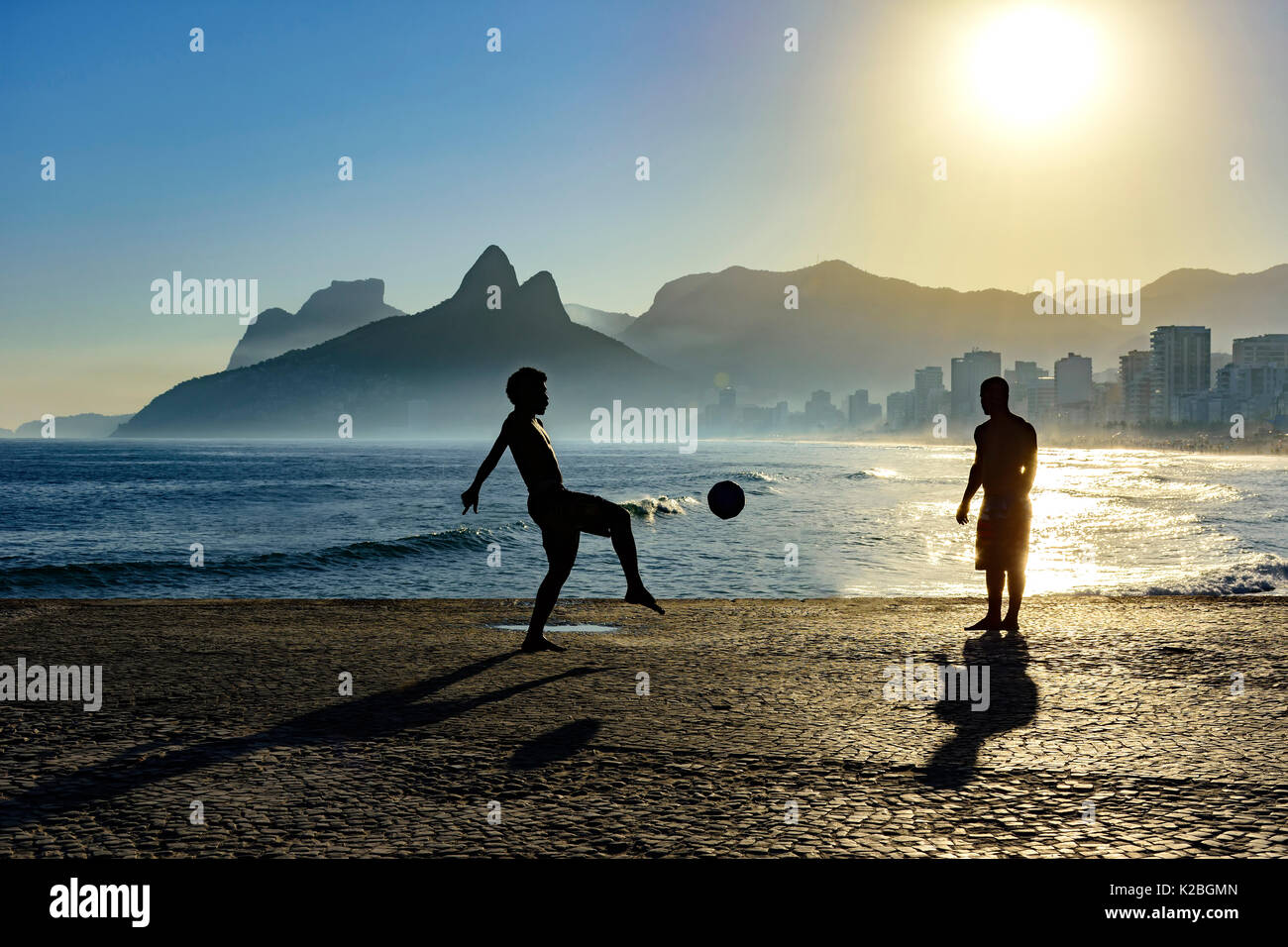 Boy playing soccer in front of the sea during sunset Stock Photo
