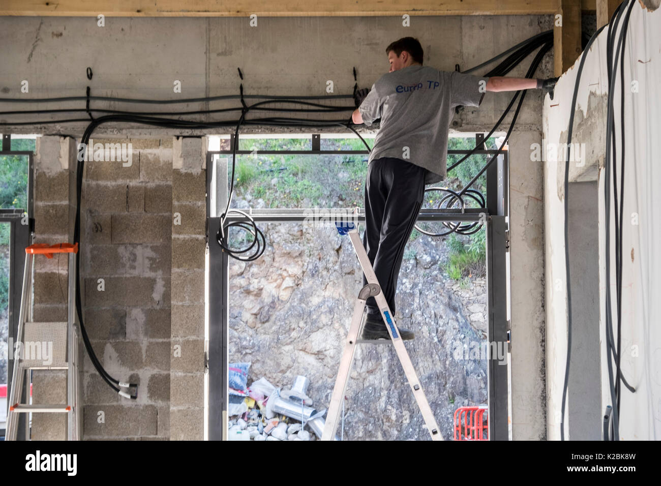 Electrician on a ladder works to install electrical cables in a new home under construction in the south of France - Stock Image