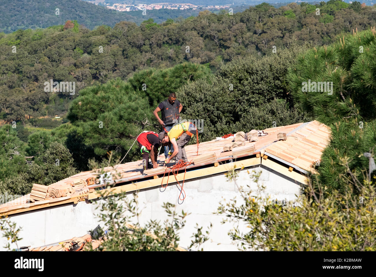 Roofers at work installing tiles on a new home in Provence, France - Stock Image