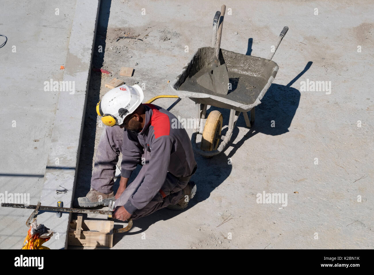 Construction laborer works on the details of building an in ground swimming pool - Stock Image