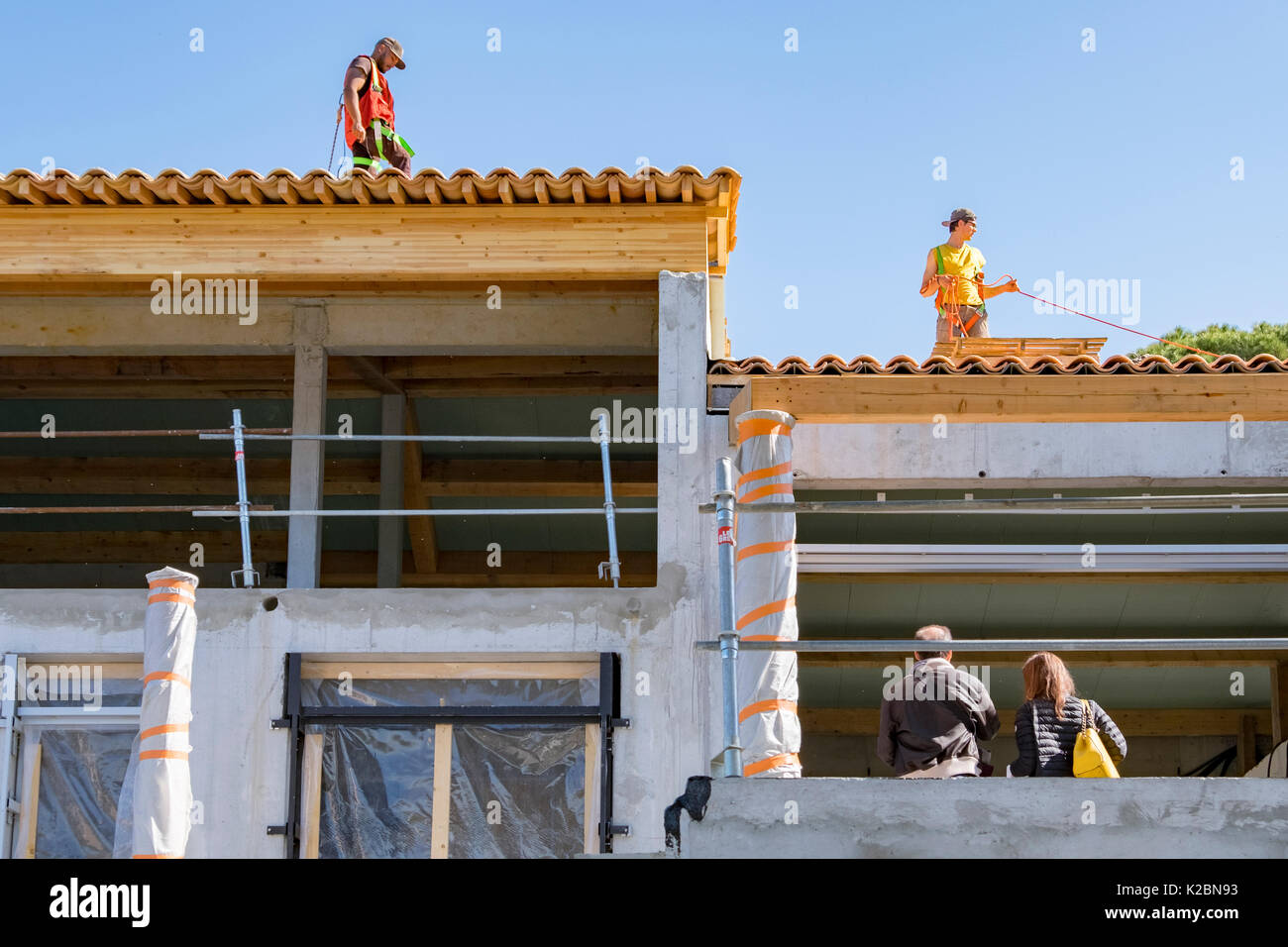 Roofers working on tiling the roof of a new house under construction on the French Riviera in southern France - Stock Image
