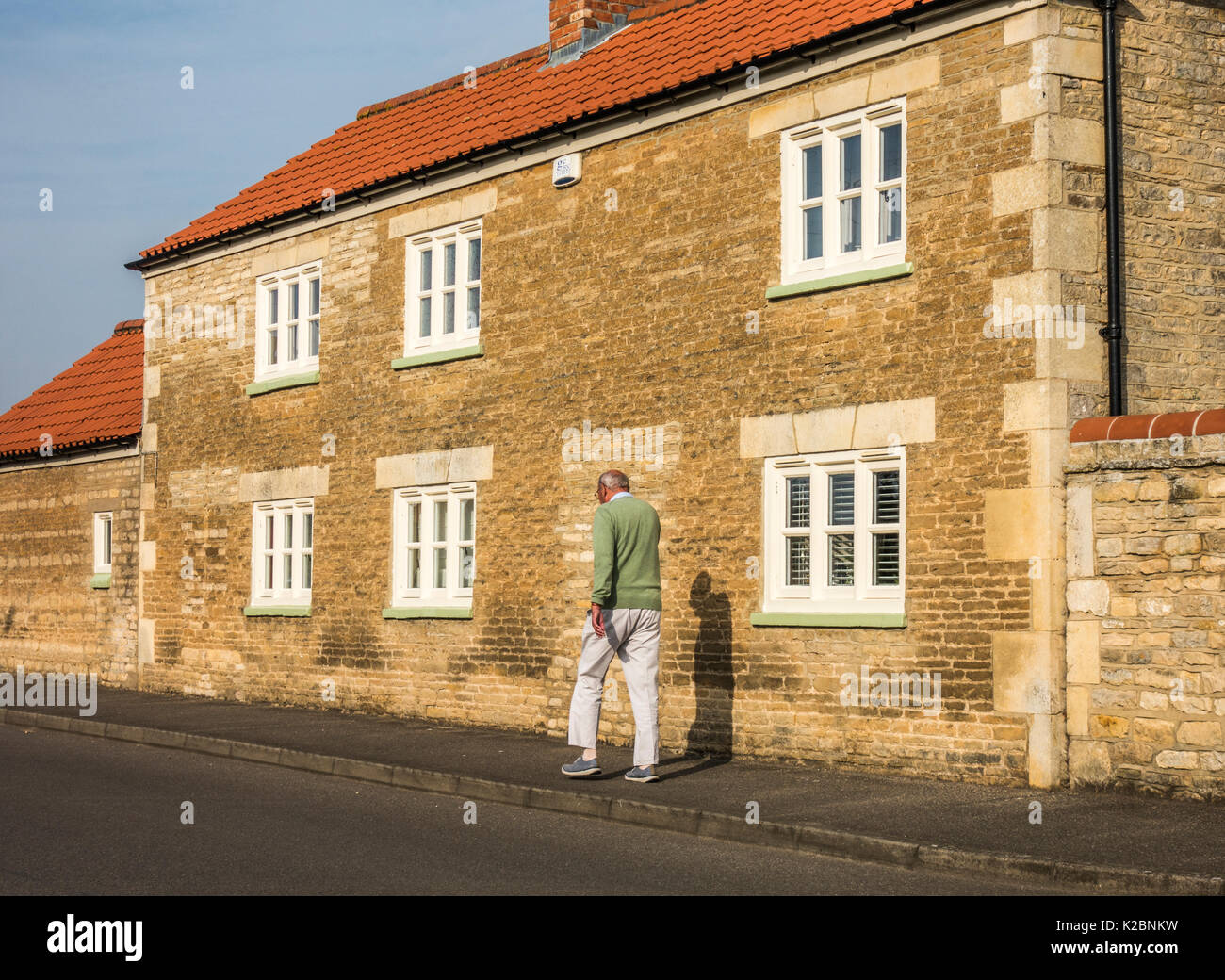 Old / senior man walking: Fit and trim elderly man taking brisk, daily walk in the warm, early morning sunshine, past an old stone house. England, UK. - Stock Image