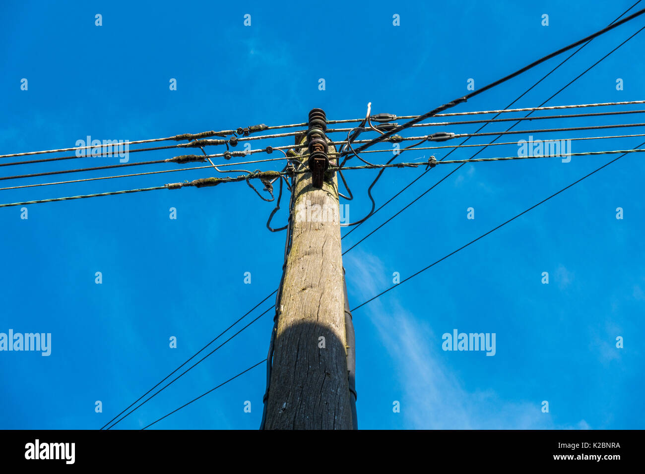 A familiar, traditional, sunlit telegraph pole and telephone cables, viewed from below, against a clear blue sky. Langtoft, Lincolnshire, England, UK. - Stock Image