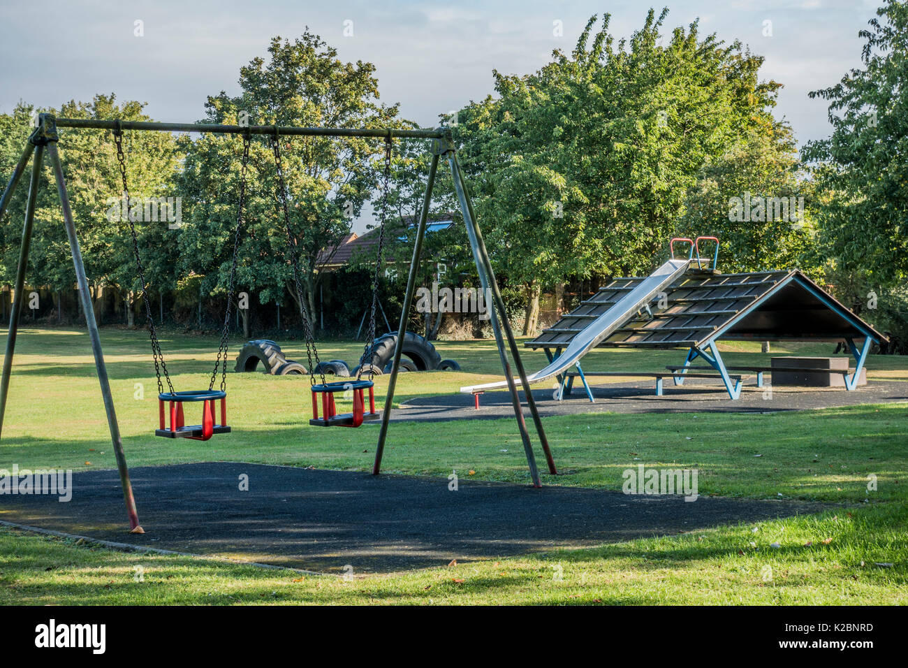 Children's playground / play park, with swings and slide, and nobody around, in the village of Langtoft, Lincolnshire, England, UK. - Stock Image