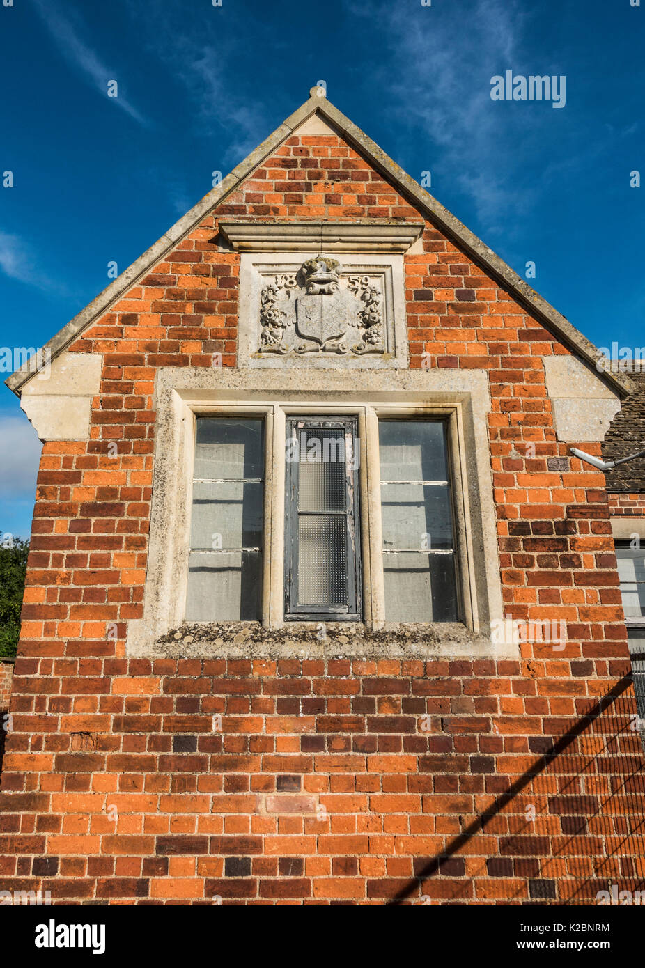 Gable wall of an old, disused village primary school, with decorative stone plaque with the 1859 year of build. Langtoft, Lincolnshire, England, UK. - Stock Image