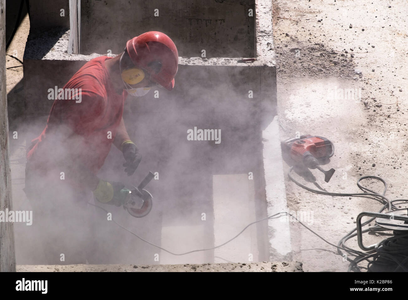 Construction worker wearing safety helmet and headphones uses a sander to sand the steps of a swimming pool - Stock Image