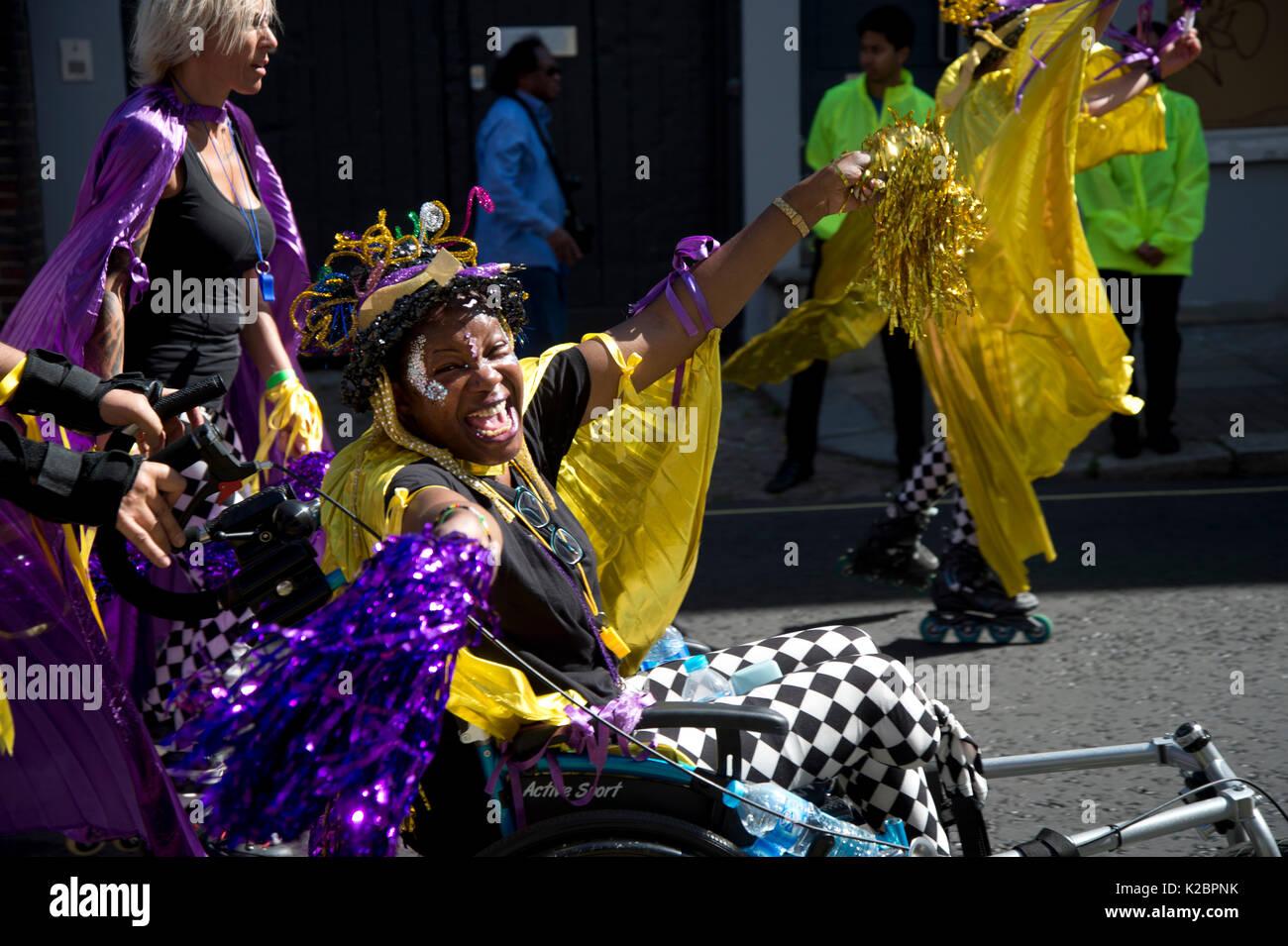 Notting Hill Carnival August  2017. A carnival reveller dances in her wheelchair, alongside a group of roller bladers. - Stock Image