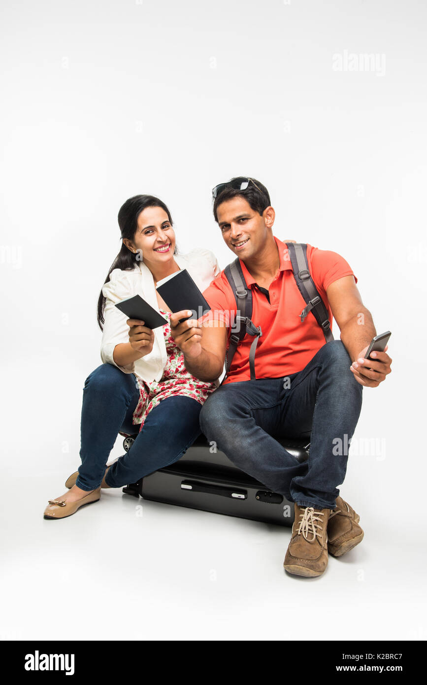 stock photo of indian young Couple packing for holiday, trying to close suitcase full with clothes, sitting isolated Stock Photo