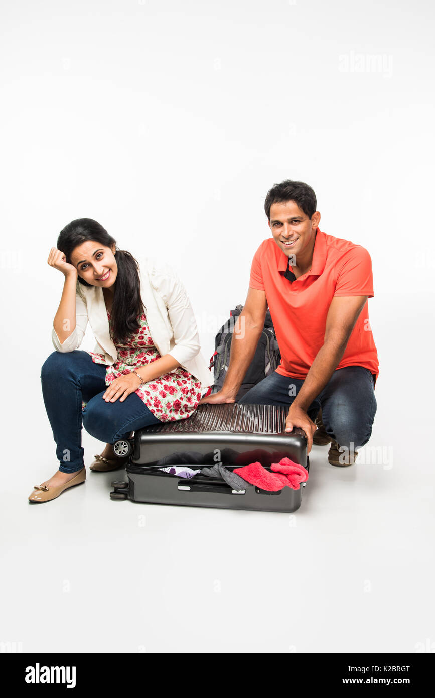stock photo of indian young Couple packing for holiday, trying to close suitcase full with clothes, sitting isolated over white background - Stock Image