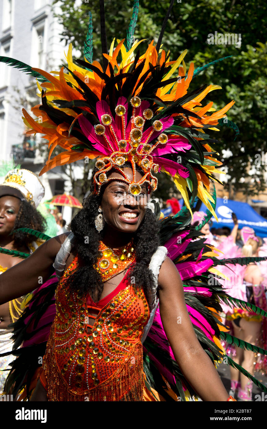 Notting Hill Carnival August 28th 2017. West London, England.Happy female dancer with feathered head dress - Stock Image