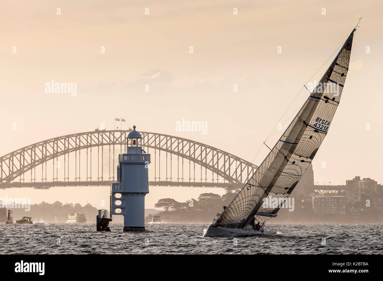 Yacht sailing past a lighthouse in front of the Harbour Bridge in Sydney, New South Wales, Australia, November 2012. All non-editorial uses must be cleared individually. - Stock Image