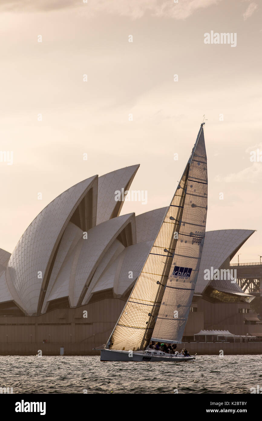 Yacht sailing past the Sydney Opera House at dusk, New South Wales, Australia, November 2012. All non-editorial uses must be cleared individually. - Stock Image