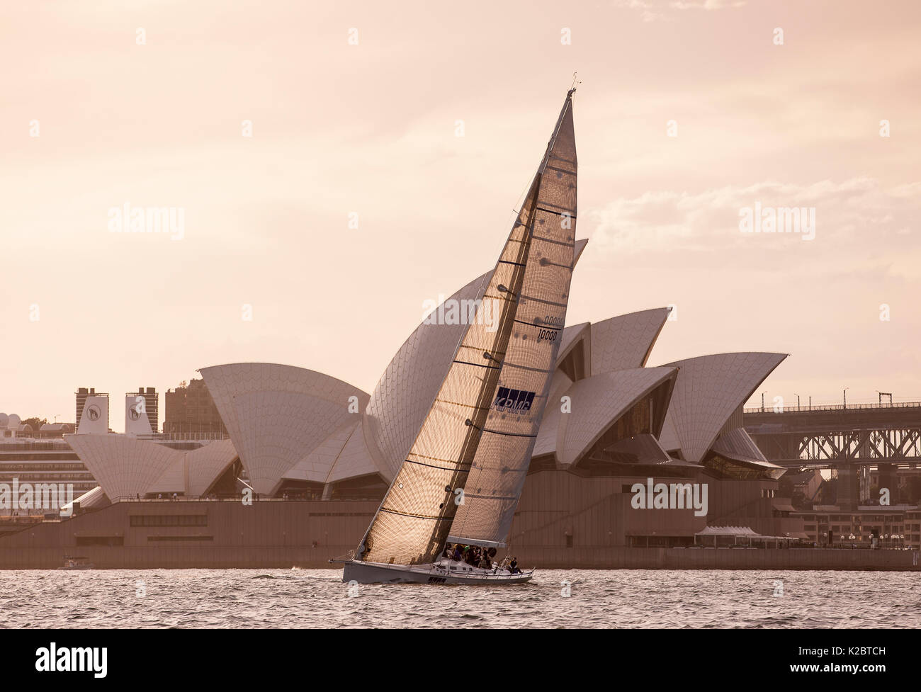 Yacht sailing past the Sydney Opera House at dusk, November 2012. All non-editorial uses must be cleared individually. - Stock Image