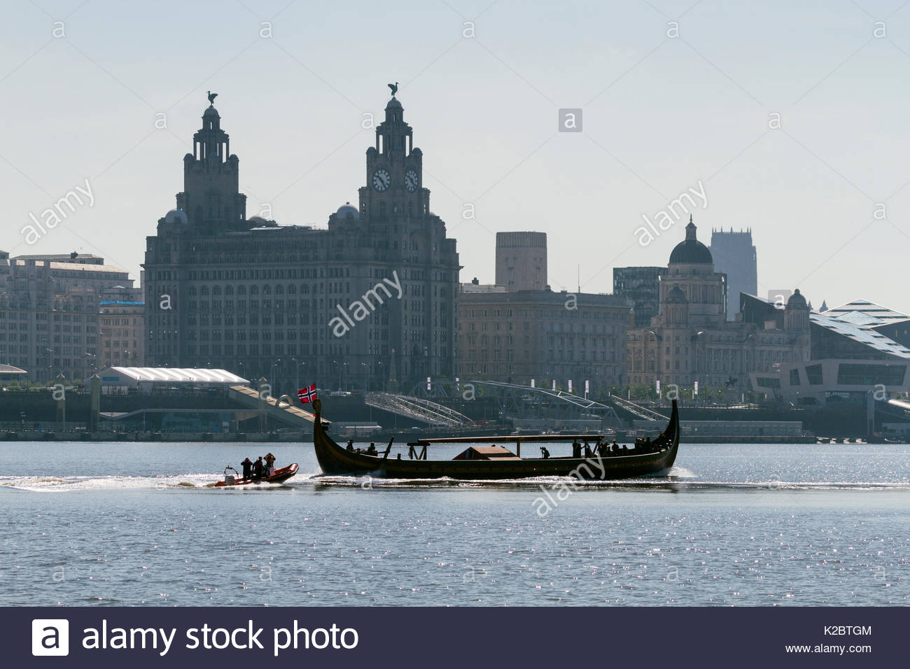Draken Harald Harfagre (Dragon Harald Fairhair), passing by the Three Graces, Royal Liver buildings, Cunard and Port of Liverpool buildings. This is the largest Viking ship built in modern times, arriving to have her mast repaired. River Mersey, Merseyside, United Kingdom, July 2014. All non-editorial uses must be cleared individually. - Stock Image