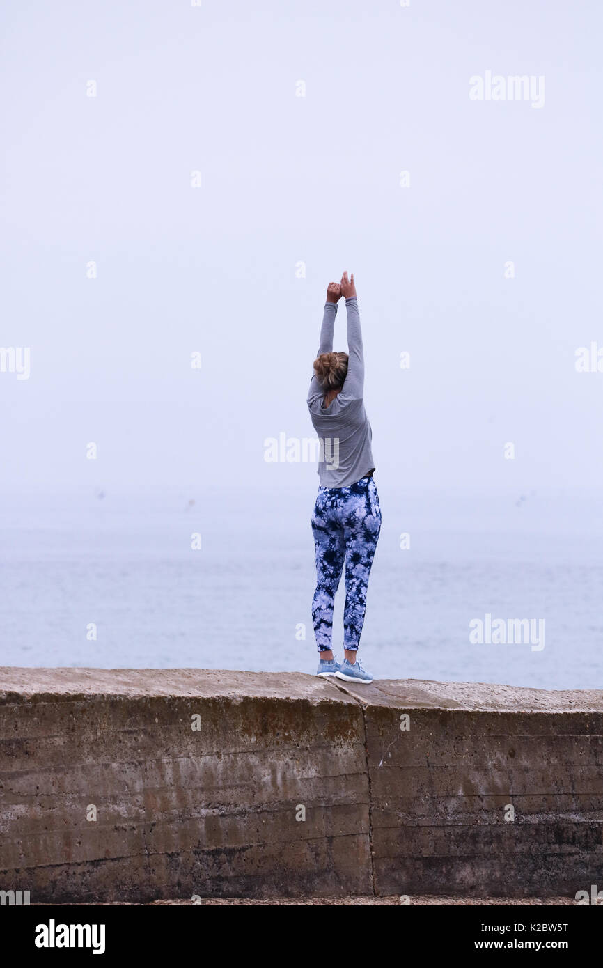 Young Woman doing yoga on sea wall in Cromer, Norfolk, UK. Stock Photo