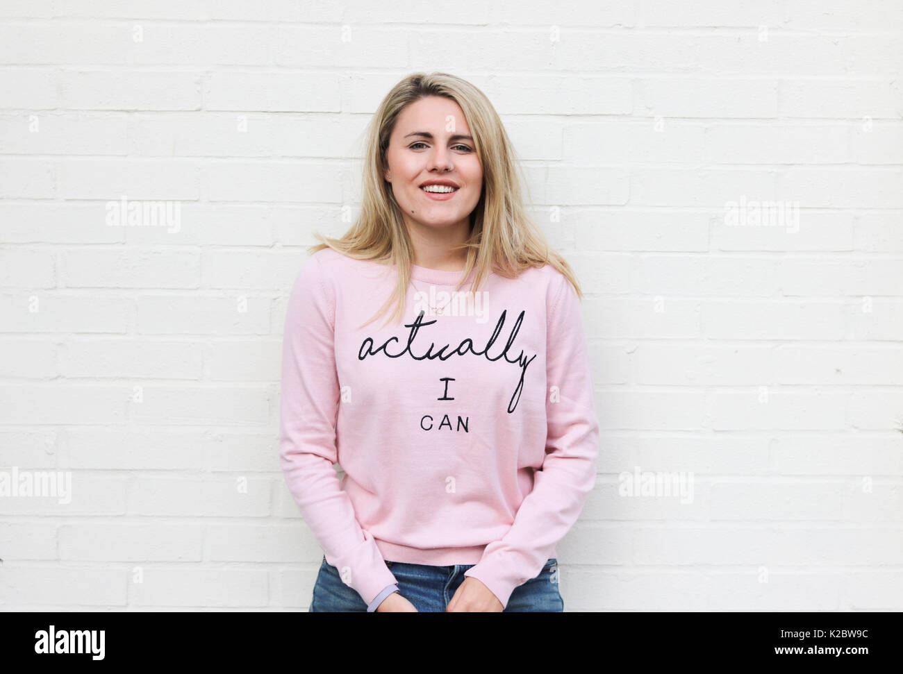 Young blonde woman in her early twenties wearing motivational jumper - Stock Image