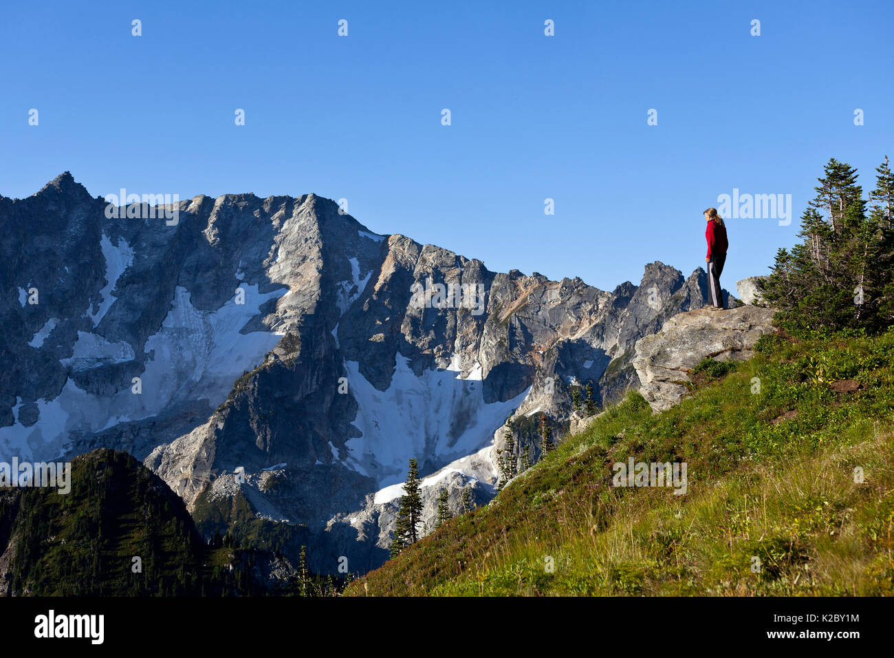 Woman looking at view, Cascade Mountains, Liberty Cap, Buck Creek Pass, Glacier Peak Wilderness, Wenatchee National Forest, Washington, USA. September 2014. - Stock Image