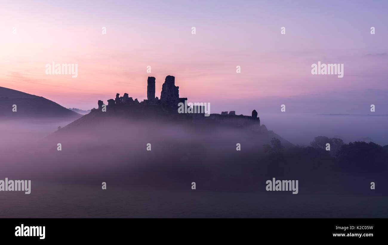 Corfe Castle at dawn on misty morning, Corfe, Dorset, UK. September 2014. - Stock Image