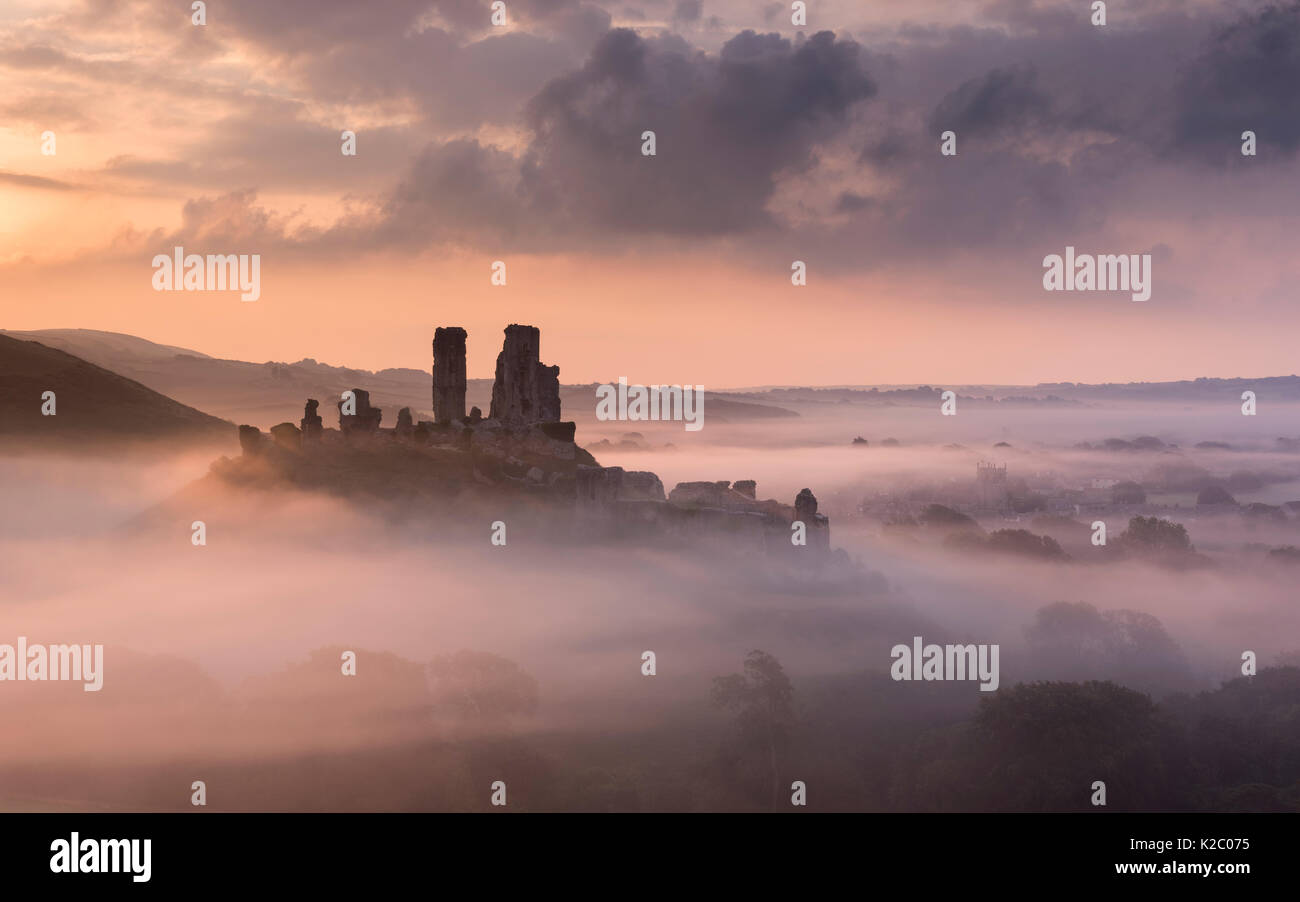Corfe castle and village in morning mist, Corfe Castle, The Purbecks, Dorset, UK. September 2014. - Stock Image