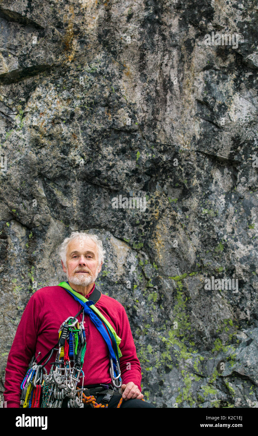 A portrait of a mature man readying himself to go rock climbing. - Stock Image