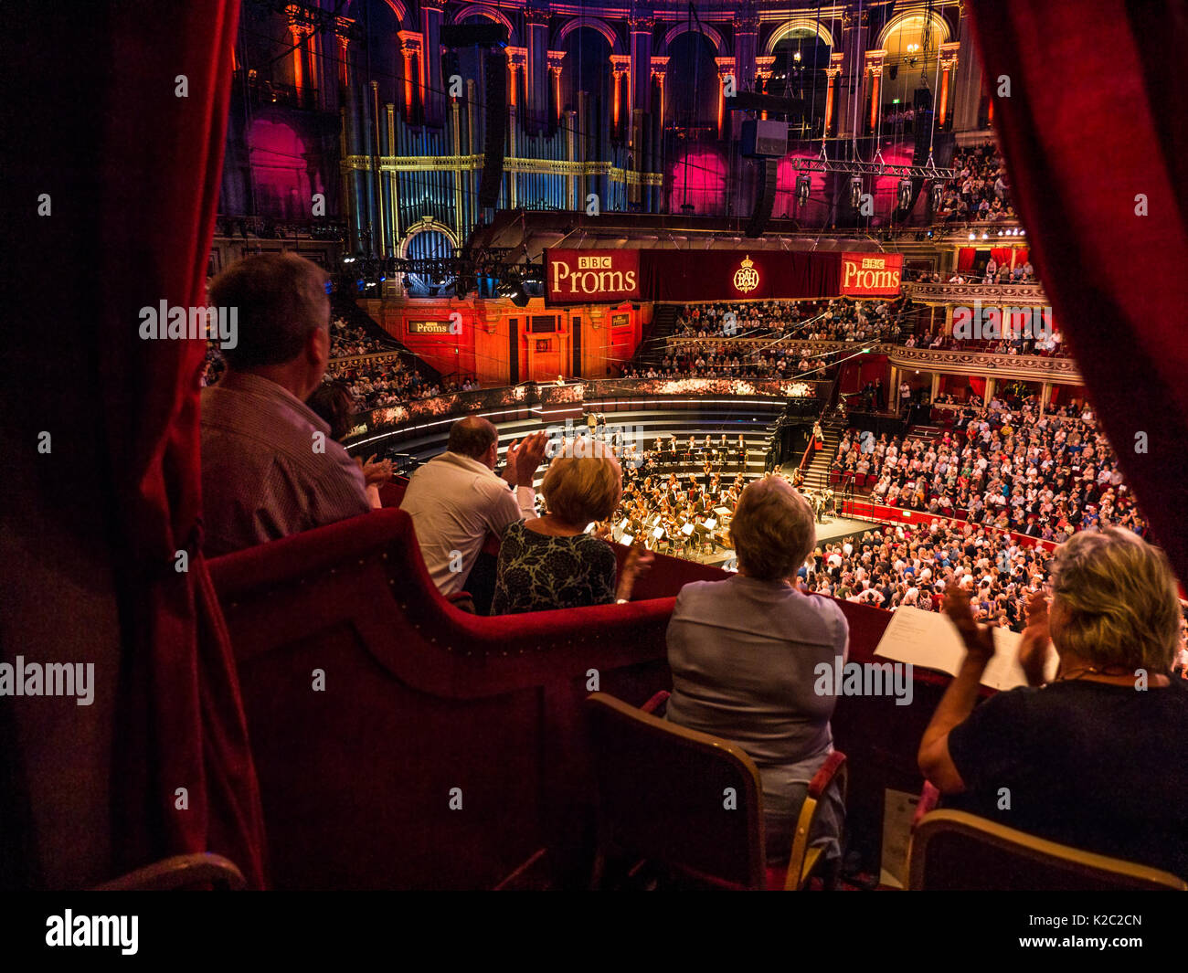 ALBERT HALL INTERIOR BBC PROMS Performance with audience applauding/clapping elevated view from luxury red velour private box to audience and orchestra stage dais behind - Stock Image