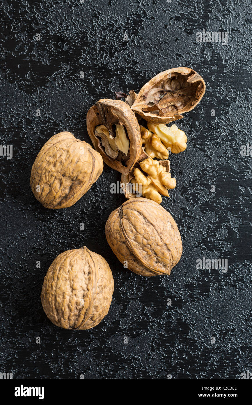 Cracked dried walnuts on black table. - Stock Image