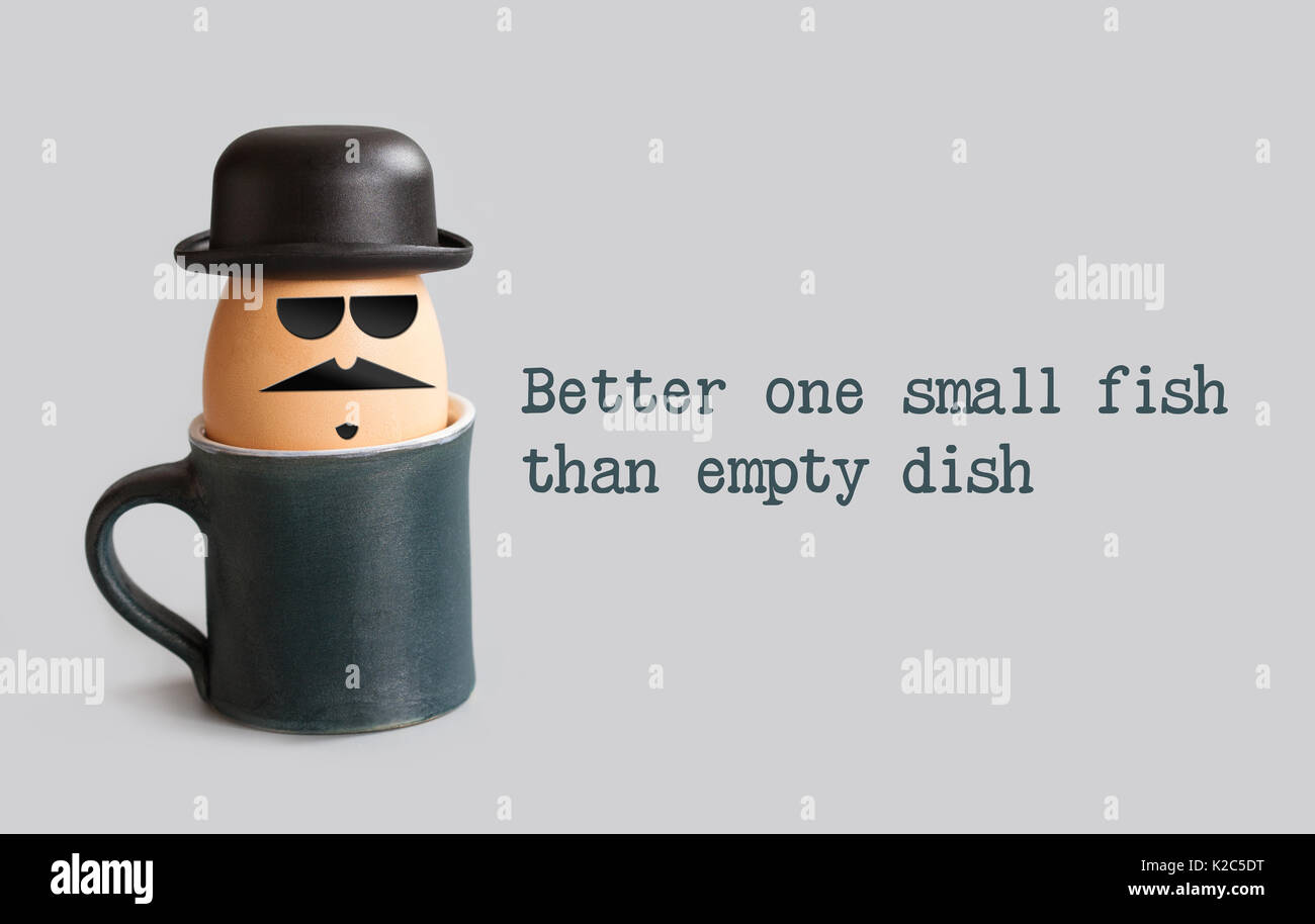 Better one small fish than empty dish. Proverbs metaphorical phrase and egg character with drawn gentleman face. Mustache, beard, black bowler hat, glasses. gray background - Stock Image