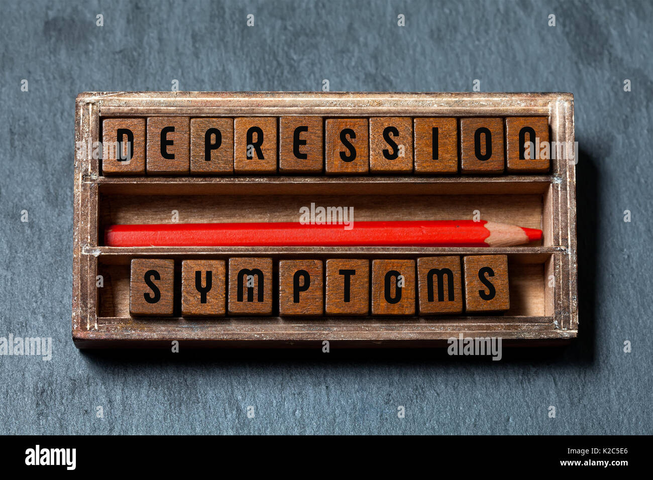 Depression symptoms conceptual image. Vintage box with textured wooden blocks letters text, red pencil. Gray stone background, macro view, soft focus - Stock Image
